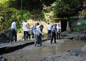 滝つぼに塩や酒などをまき、行楽の安全を祈願した市観光協会の役員ら=小城市小城町の清水の滝