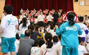 演奏に合わせ踊る吹奏楽部員を真似し、立ち上がって一緒に踊る児童ら=大和特別支援学校