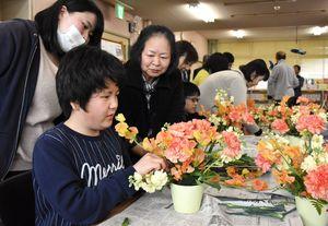 花の手触りや香りを楽しみながら、花を生ける児童生徒ら=佐賀市の県立盲学校