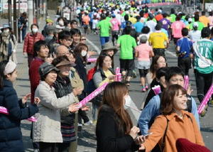 スタートするランナーたちを応援する沿道の人たち=佐賀市の県総合運動場前