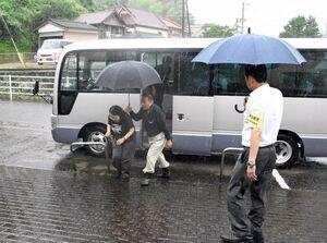 新たな投票所への送迎バスを利用して投票に向かう女性(左)=武雄市の若木公民館