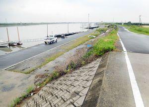 かさ上げ工事を終えた堤防(手前)と、古いままの共有地の部分(奥)には、くっきりと境目がある=佐賀市の早津江漁港