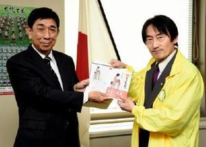 古谷宏県教育長(左)にDVDなどを手渡す、みらいプラネットの有富健理事長=佐賀県庁
