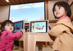 タブレットで色を塗った「凌風丸」を大型スクリーン(奥)に映し出すことができる=佐賀市の佐賀城本丸歴史館