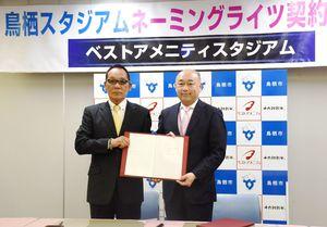 来年のネーミングライツ契約を結んだ内田社長(左)と橋本市長=鳥栖市のベストアメニティスタジアム