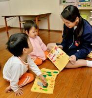 手作りのおもちゃで乳幼児と遊ぶ生徒=上峰町のひかり保育園