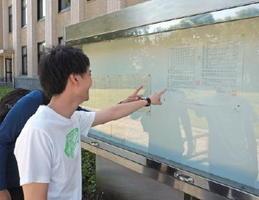 県庁旧館玄関前に張り出された合格者の受験番号を見る受験者=佐賀県庁