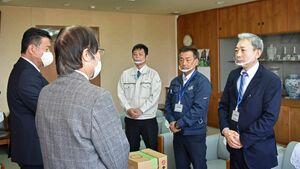 透明マスクや消毒液を伊万里市に寄贈した亀栄グループの前田省吾社長(右)。社長が装着しているのが透明マスク=市役所