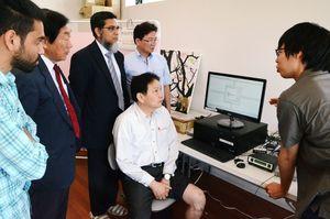 膝関節につけたセンサーで音を感知し、診断する新装置。左から2人目が吉村社長、3人目がイスラム・カーン准教授=佐賀市東与賀町の大神