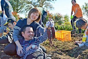 サツマイモを掘り、笑顔を見せる利用者=佐賀市久保泉町のやまぐち薬局農園