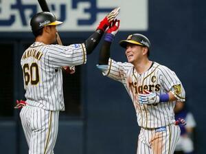 6回、本塁打を放ち次打者中谷(左)とタッチを交わす阪神・糸原=京セラドーム