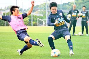 クラブとして初のグループステージ突破を目指し、練習で激しく競り合うMF松岡(左)とDF安在(中央)=鳥栖市北部グラウンド