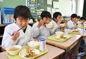 (5)天衝米のご飯をおいしそうに食べる児童=上峰小(13日付17面)