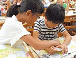 マンホールメモ帳に書かれた市町を地図帳で探す子どもたち=佐賀市の赤松小学校