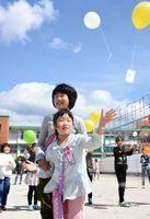 「若楠校区、全員集合!」とのかけ声とともに風船を大空へ飛ばす子どもたち=佐賀市若宮の若楠小学校