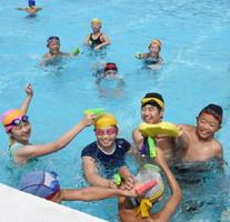 プールでのゲームを歓声を上げて楽しむ雄武町と武内小の子どもたち=武雄市の武内小