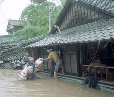 2メートル以上浸水して土砂が流れ込み、倒壊した家屋の2階から衣類などを運び出す住人=平成2年7月2日、塩田町