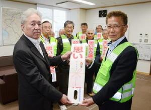 森孝輝理事長(左)からポップを受け取る鶴田正興会長=鹿島署