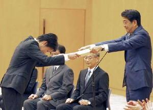 安倍首相から感謝状を授与される佐賀市の山田健太郎さん=13日午後、首相官邸