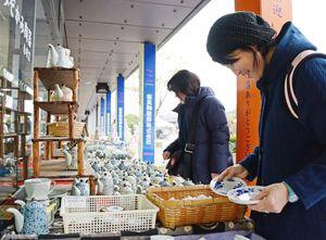 一枚一枚手にとってお気に入りの商品を探す来場者=有田町の有田陶磁の里プラザ