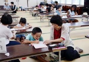 元教師のサポートを受けながら夏休みの宿題に励む子どもたち=神埼市中央公民館