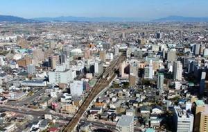 ドローンで撮影した佐賀駅(中央部)周辺。1970年代に高架化を終え、新たな用地を生み出しにくい環境にある=佐賀市