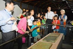 現地ガイドの説明を聞きながら、武寧王の墓から見つかった石版を見学する児童生徒=中清南道公州市の熊津百済文化歴史館