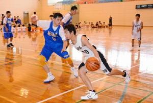 実業団選手に果敢にドリブルを仕掛ける生徒=東松浦郡玄海町の社会体育館
