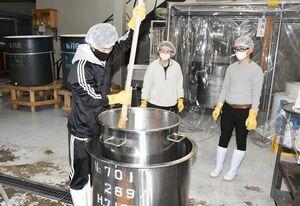 酒母を造るタンクに蒸した米や酵母菌、水などを入れ、櫂でかき混ぜる佐賀大生=基山町の基山商店
