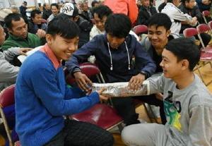 訓練には黒川町内で働くインドネシアの若者16人も参加し、新聞紙とラップを使った応急手当ての方法を実践した=黒川公民館