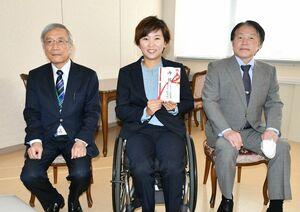 お祝いを手に笑顔を見せる大谷桃子選手(中央)。左は福元裕二理事長、右は久木野憲司学長=神埼市の西九州大