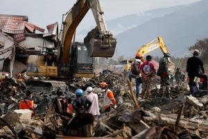 インドネシア・中スラウェシ州の州都パル近郊で活動する不明者の捜索チーム=11日(ロイター=共同)