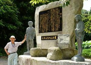 にあんちゃんの記念碑の前で思い出を語る山口駿一さん=唐津市肥前町
