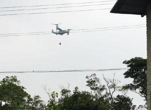 物体をつり下げて飛行する米軍の新型輸送機オスプレイ=6日午後、沖縄県宜野座村(宜野座村提供)