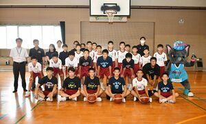 贈られたボールを手に写真に収まる德川選手と城南中バスケ部の選手たち=佐賀市の城南中