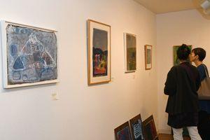 諸江さんがクレヨンや水彩で描いた抽象画など約80点が並ぶ=佐賀市松原のギャラリーシルクロ