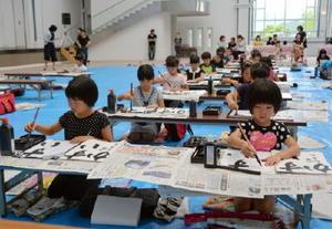 真剣な表情で半紙に向かう小学生=有田町の?の博記念堂