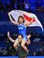 女子57キロ級で優勝し、肩車で日の丸を掲げる川井梨紗子=ヌルスルタン(共同)