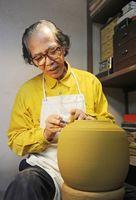 ろくろで彫りを入れる中島宏さん。バッハなどクラシックを聴きながら没頭することが多かった=2011年5月、武雄市西川登町の弓野窯