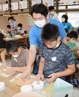 北川朝行さん(中央)の指導で、石こう型に陶土を詰めて箸置きを作る児童たち=有田町泉山の体験工房ろくろ座