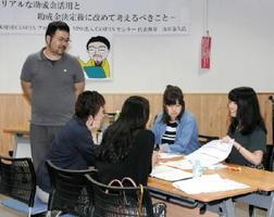 講師の山田泰久さん(左)からアドバイスを受けながら、ワークショップで事業づくりに取り組む参加者=佐賀市の佐賀市民活動プラザ