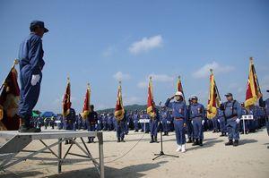 市内9支団が一堂に会して開かれた第1回唐津市消防団操法大会。開会式では団員たちが気合のこもった敬礼を見せた=7月、同市の松浦川運動広場