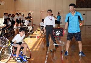 プロコーチの吉永寛和さん(右)の指導で車いすテニスを体験する児童=鳥栖市の旭小