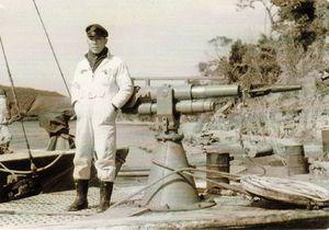 塩見伊一さんと今回寄贈した捕鯨砲=昭和32年ごろ、興福丸船上(塩見さん提供)