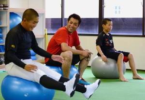 バランスボールの使い方などを笑顔で指導する吉川輝昭さん(中央)=佐賀市内