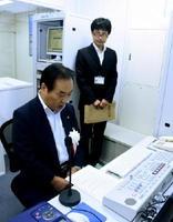 防災無線局の開局で第一声の試験音声を読み上げる塚部芳和市長=伊万里市役所
