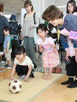 会場に設置されたブースで、ボールを転がして遊ぶ子ども=佐賀市諸富町の市産業振興会館