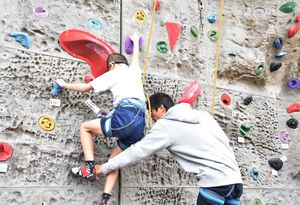 生徒から手や足の運び方を教わりながら、壁を登る児童=多久市の多久高