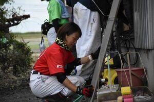 油や泥で汚れた網戸を洗う「IVUSA」のメンバー=杵島郡大町町福母