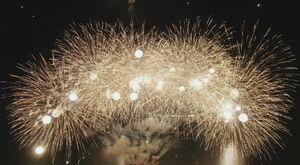次々と打ち上がる花火が辺りを明るく照らしだす(ドローンで空撮)